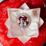Pliage de la serviette en forme de fleur de lotus avec le cadeau des invités posé dessus.